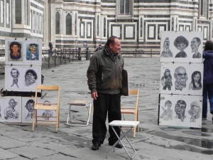 A caricature artist waits outside the Cattedrale di Santa Maria del Fiore as the next throng of tourists exits.